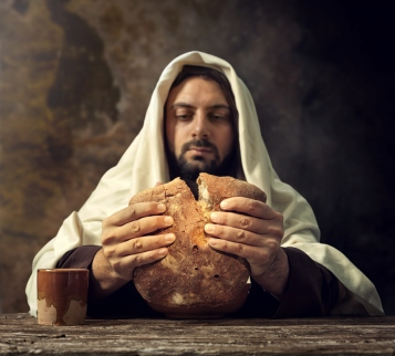 Man in cloak tearing bread into two