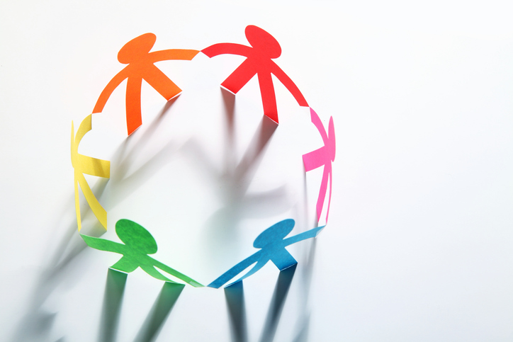 Paper cutouts of colorful people holding hands in a circle